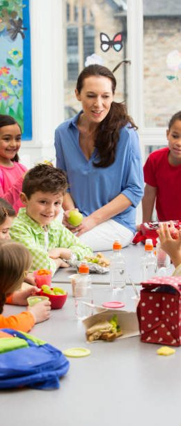 Mixed group of ethnic kids having lunch with teacher